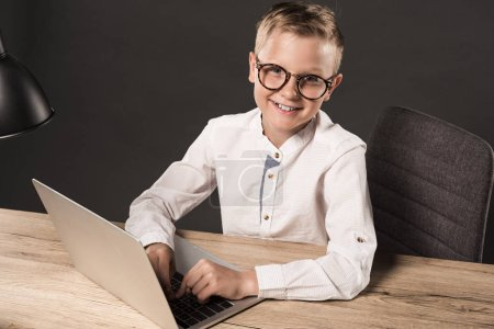 happy little boy in eyeglasses looking at camera while sitting at table with laptop and lamp on grey background