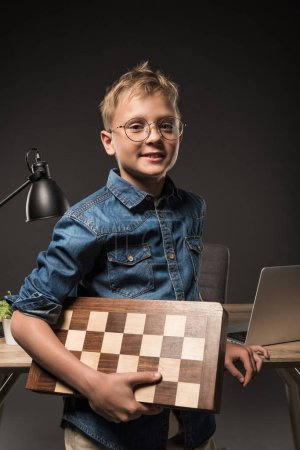 smiling little boy in eyeglasses holding chessboard near table with laptop and lamp on grey background