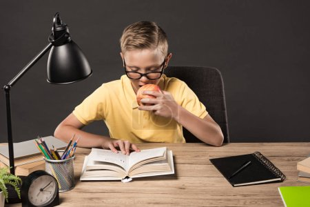 schoolboy in eyeglasses eating apple and reading book at table with lamp, books, clock, colour  pencils and textbooks on grey background
