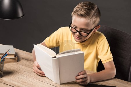 schoolboy in eyeglasses reading book at table with lamp, colour pencils and stack of books on grey background