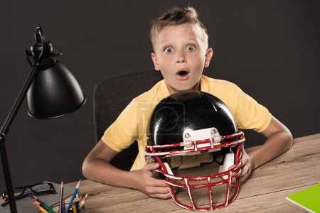 shocked schoolboy sitting with american football helmet at table with eyeglasses, lamp, colour pencils and books on grey background