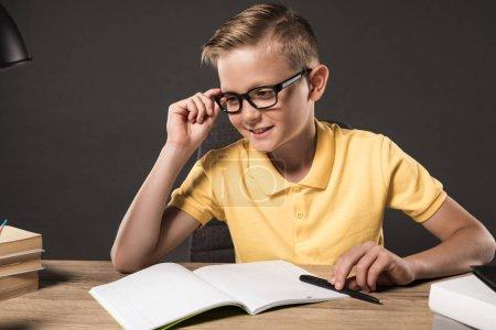 Photo pour Écolier souriant dans des lunettes regardant loin tout en faisant des devoirs à table avec pile de livres, manuels et lampe sur fond gris - image libre de droit