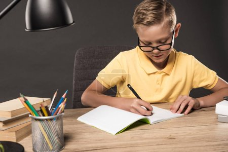 Photo for Focused schoolboy doing homework in textbook at table with colour pencils, lamp and stack of books on grey background - Royalty Free Image
