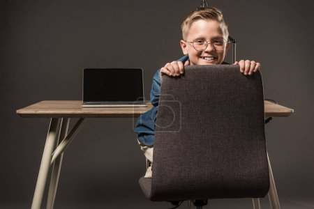 happy little boy sitting on chair and looking at camera near table with lamp and laptop on grey background