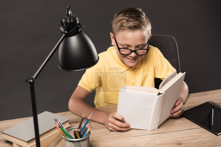 schoolboy in eyeglasses reading book at table with colour pencils, books, textbook and lamp on grey background