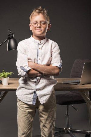 Photo pour Petit garçon à lunettes avec les mains croisées, debout près de table usine, ordinateur portable et lampe sur fond gris - image libre de droit