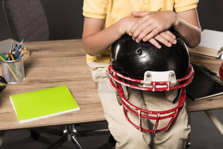 cropped image of schoolboy holding american football helmet and sitting on table with books, colour pencils and textbook on grey background
