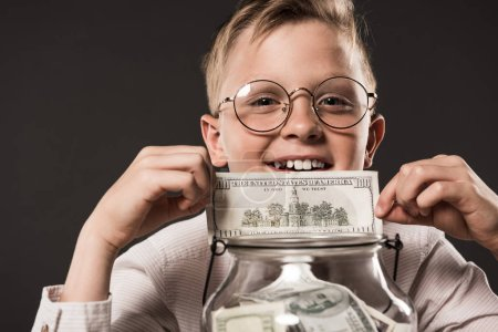 portrait of smiling little boy in eyeglasses showing dollar banknote over jar full of cash money isolated on grey background