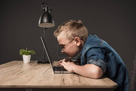 side view of little boy in eyeglasses using laptop at table with lamp and plant on grey background