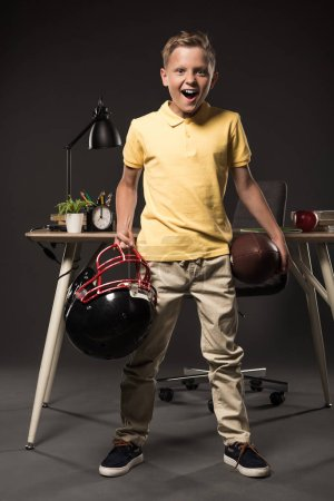 excited screaming schoolboy holding american football helmet with ball and standing near table with books, plant, lamp, colour pencils, apple, clock and textbook on grey background