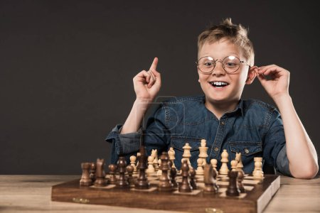 happy little boy in eyeglasses doing idea gesture by finger at table with chess board isolated on grey background