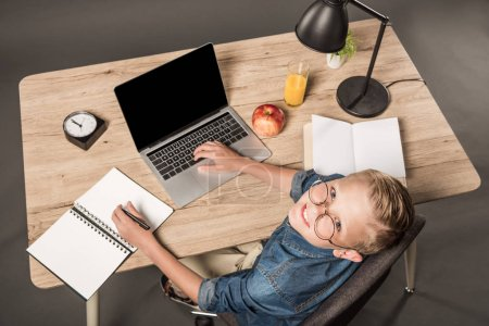 overhead view of school boy in eyeglasses looking at camera while doing homework at table with laptop, textbook, apple, juice, lamp, plant, clock and book