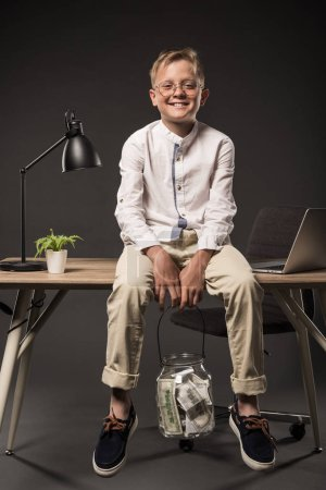happy little boy in eyeglasses with jar full of dollar banknotes sitting on table with lamp, plant and laptop on grey background