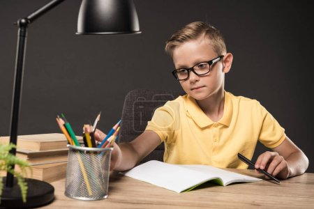 serious schoolboy in eyeglasses doing homework at table with colour pencils, books, lamp and textbook on grey background