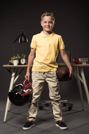 adorable schoolboy holding american football helmet with ball and standing near table with books, plant, lamp, colour pencils, apple, clock and textbook on grey background