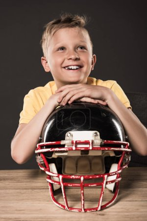 dreamy happy little boy sitting with american football helmet at table on grey background