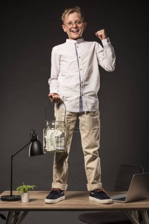 happy little boy in eyeglasses holding jar full of dollar banknotes and gesturing by hand while standing on table with laptop, plant and lamp on grey background
