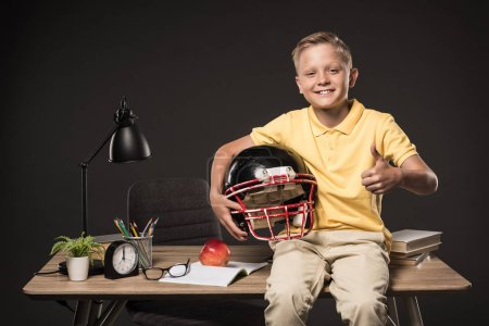 schoolboy holding american football helmet, doing thumb up gesture and sitting on table with books, eyeglasses, plant, lamp, colour pencils, apple, clock and textbook on grey background