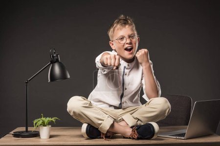 excited little boy in eyeglasses fighting by fists while sitting on table with lamp, plant and laptop on grey background