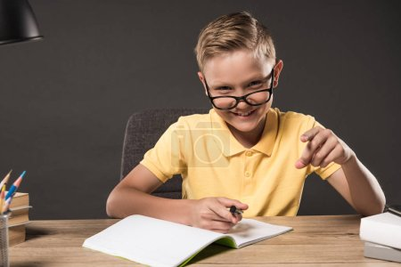 smiling schoolboy in eyeglass pointing by finger and doing homework at table with books, colour pencils and textbook on grey background