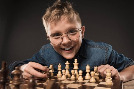 smiling little boy in eyeglasses playing chess isolated on grey background