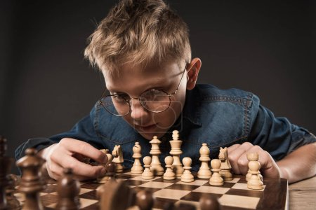 focused little boy in eyeglasses playing chess at table isolated on grey background
