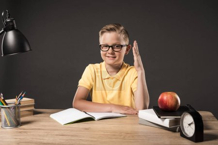 smiling schoolboy with raised hand sitting at table with clock, lamp, colour pencils, books, textbooks and apple on grey background
