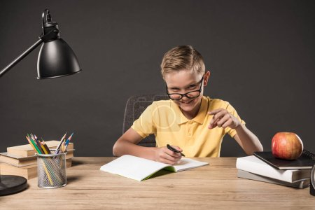 happy schoolboy in eyeglass pointing by finger and doing homework at table with lamp, books, colour pencils and textbook on grey background