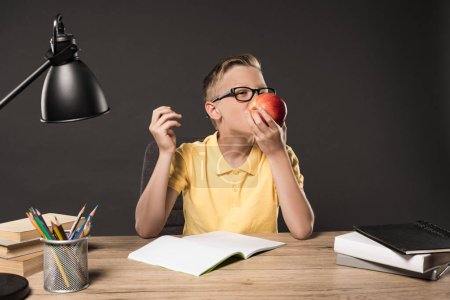 Photo for Schoolboy in eyeglass eating apple and doing homework at table with lamp, books, colour pencils and textbook on grey background - Royalty Free Image