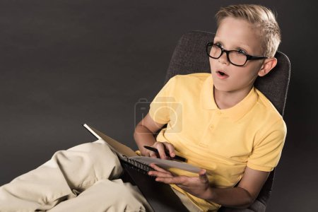 shocked schoolboy in eyeglasses sitting on chair and doing homework with textbook on grey background