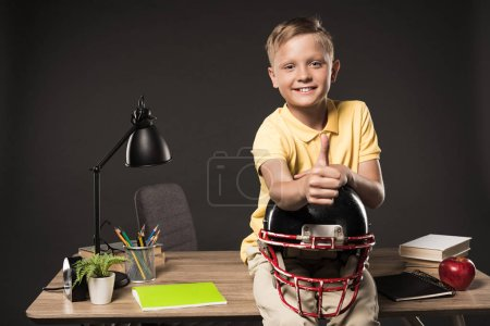 happy schoolboy holding american football helmet, doing thumb up gesture and sitting on table with books, plant, lamp, colour pencils, apple, clock and textbook on grey background