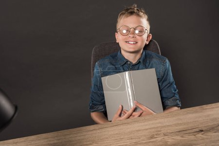 smiling schoolboy with closed eyes in eyeglasses holding book at table with lamp on grey background