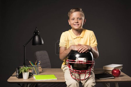 smiling schoolboy holding american football helmet and sitting on table with books, plant, lamp, colour pencils, apple, clock and textbook on grey background