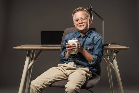 smiling little boy in eyeglasses sitting on chair with coffee cup near table with laptop and lamp on grey background