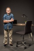 little boy in eyeglasses standing with crossed hands near table with laptop, book and lamp