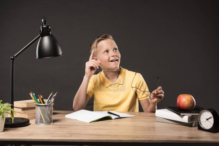 schoolboy holding eyeglasses and doing idea gesture by finger at table with books, plant, lamp, colour pencils, apple, clock and textbook on grey background