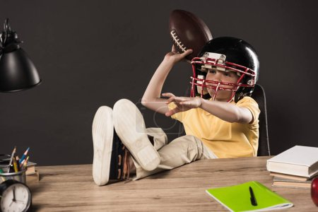 schoolboy in american football helmet throwing ball and sitting with legs on table with books, plant, lamp, colour pencils, apple, clock and textbook on grey background