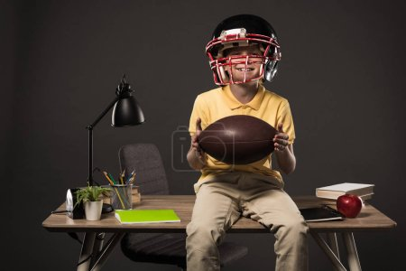 smiling schoolboy in american football helmet holding ball and sitting on table with books, plant, lamp, colour pencils, apple, clock and textbook on grey background