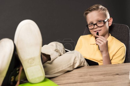 schoolboy in eyeglasses with textbook doing homework with legs on table on grey background