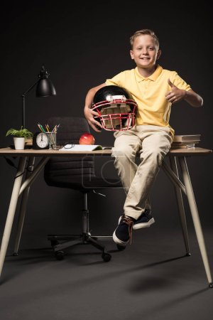 adorable schoolboy holding american football helmet, doing thumb up gesture and sitting on table with books, plant, eyeglasses, lamp, colour pencils, apple, clock and textbook on grey background