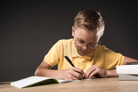 focused schoolboy in eyeglasses writing in textbook at table with stack of books on grey background