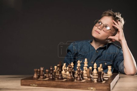 thoughtful little boy in eyeglasses sitting at table with chess board on grey background