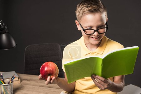 smiling schoolboy in eyeglasses holding apple and doing homework near table with colour pencils, lamp and books on grey background