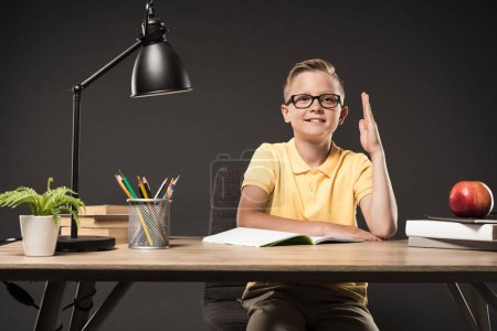 schoolboy in eyeglasses sitting with raised hand at table with books, plant, lamp, colour pencils, apple and textbook on grey background