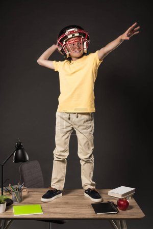 smiling schoolboy in american football helmet imagining that he throwing ball and standing on table with books, plant, lamp, colour pencils, apple, clock and textbook on grey background