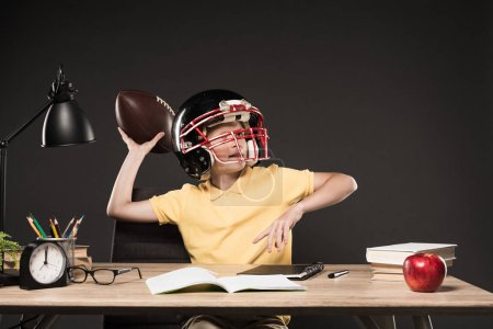 schoolboy in american football helmet throwing ball and sitting at table with books, plant, lamp, colour pencils, apple, clock and textbook on grey background