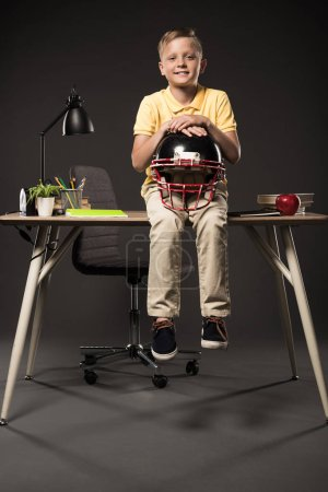Photo for Smiling schoolboy holding american football helmet and sitting on table with books, plant, lamp, colour pencils, apple, clock and textbook on grey background - Royalty Free Image