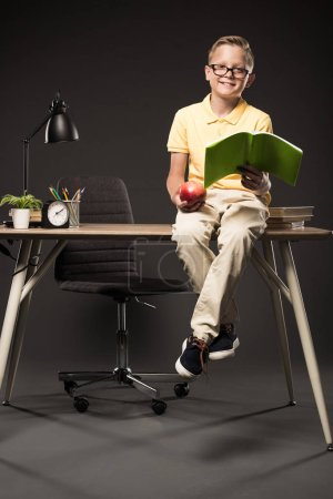 smiling schoolboy holding apple and doing homework while sitting on table with books, plant, lamp, colour pencils, clock and textbook on grey background