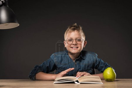happy schoolboy reading book at table with lamp and pear on grey background
