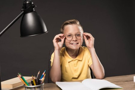smiling schoolboy adjusting eyeglasses and sitting at table with lamp, colour pencils, books and textbook on grey background